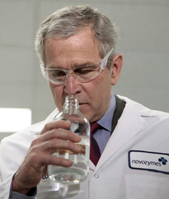 U.S. President George W. Bush smells a bottle of ethanol as he tours Novozymes North America Inc. with Garrett Screws, Senior Manager of Government Relations in Franklinton, North Carolina, February 22, 2007.  REUTERS/Jim Young     (UNITED STATES)